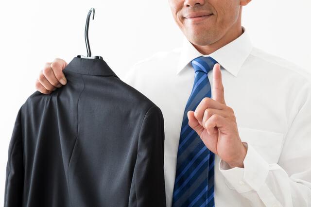 ハンガーにかけたスーツを持つ男性