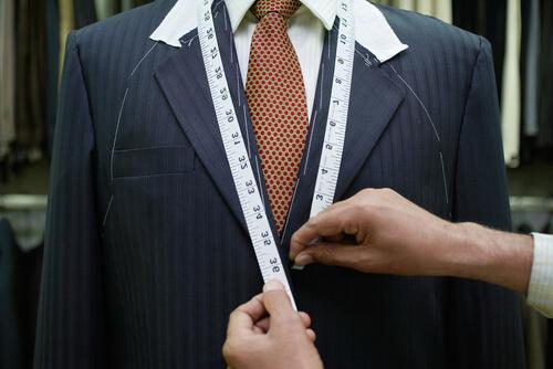 メジャーでスーツのサイズを測っているところ
