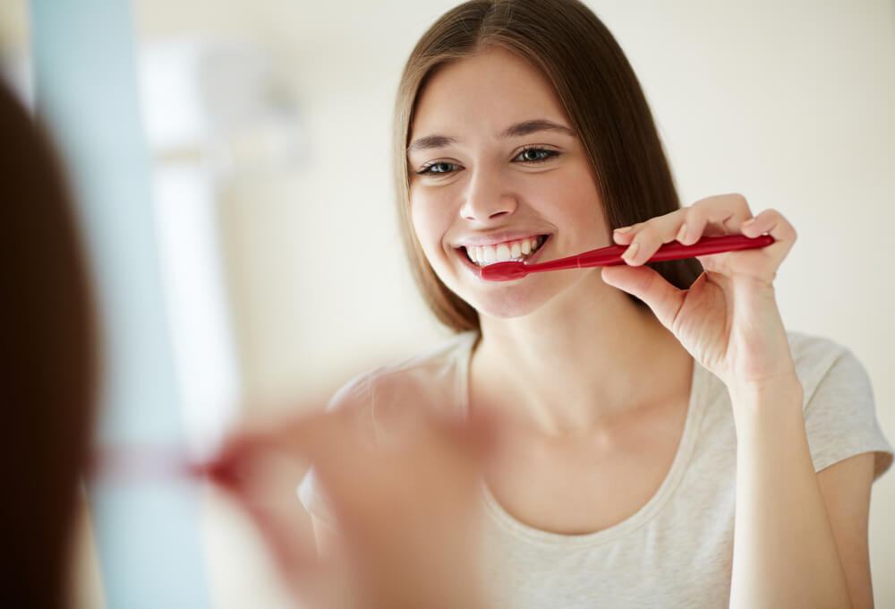 鏡の前で歯磨きをする女性