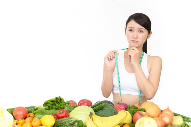 野菜の山を前に考えている女性
