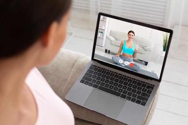 パソコン画面に映っているオンラインフィットネスのトレーナー