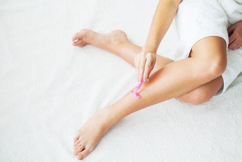 自分の足をシェービングする女性
