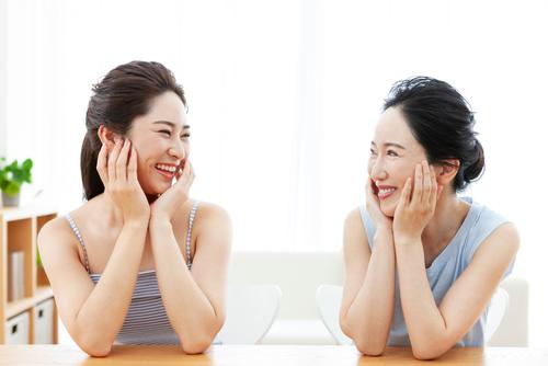 頬を両手で包んでいる女性2人