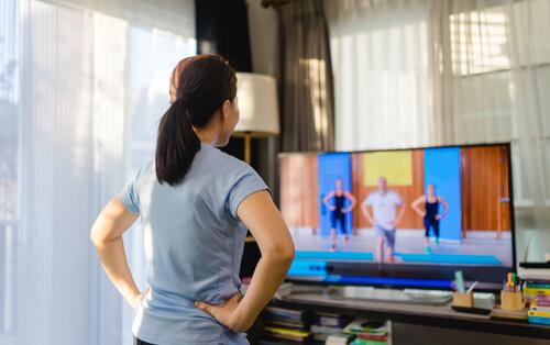テレビ画面のエクササイズを見る女性