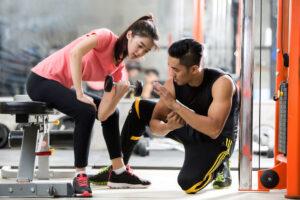 女性にトレーニングの指導をする男性
