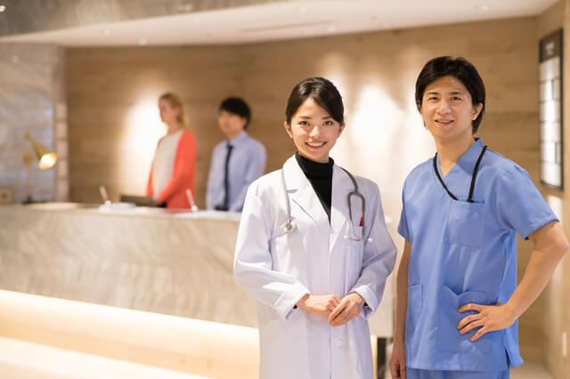 クリニックの受付に立つ男性と女性の医師