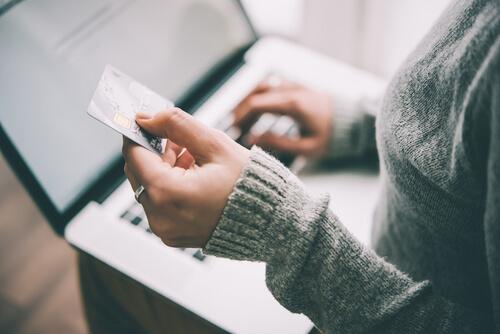 クレジットカードを手にもってPCを触る人
