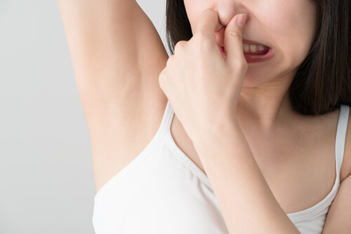 腕を上げて鼻をつまむ女性