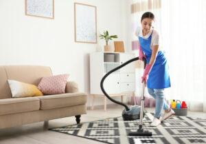 居間で掃除機をかける女性