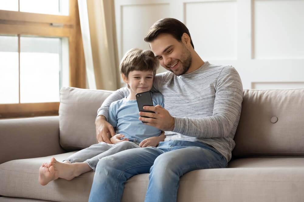 ソファの上で父親と息子がスマホを見ている