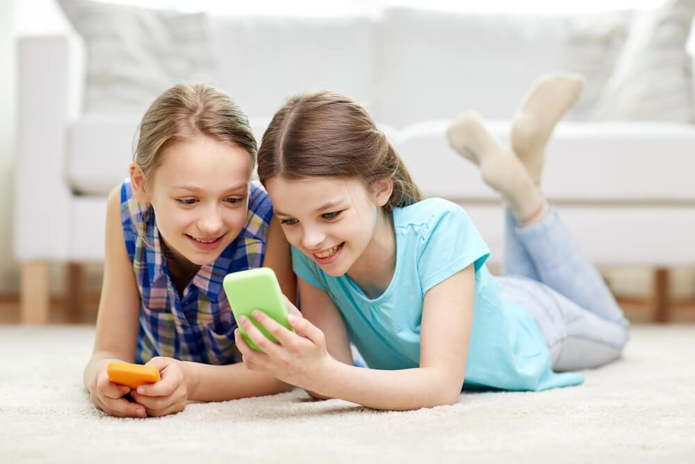 2人の女の子が横になってスマホを見ている